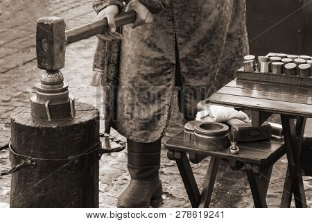 Coinage Craftsman Stamping Coins With Hammer And Anvil. Vintage Style Concept