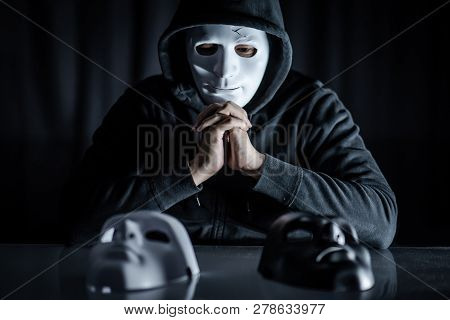 Hoodie Man Wearing Mystery Mask Choosing Black Or White Mask On The Table. Anonymous Social Masking.