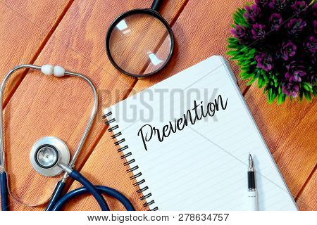 Top View Of Stethoscope,magnifying Glass,plant,pen And Notebook Written With Prevention On Wooden Ba