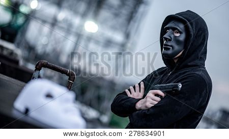 Mystery Hoodie Man In Broken Black Mask Holding Gun Feeling Guilty. Crime And Violence Concepts