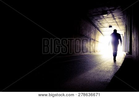 A Man Going To The End Of A Tunnel To The Light. Silhouette Of A Man Going To Light In The End Of A