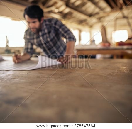 Woodworker Leaning On A Workshop Bench Reading Furniture Plans