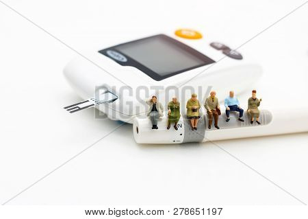 Miniature People Sitting On A Glucose Meter Of Diabetes , Business And Health Care Concept.