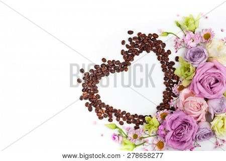 Festive concept for Valentine day or Mother's day with flowers and coffee beans in shape of heart on white background. Valentine day greeting card, top view, flat lay.