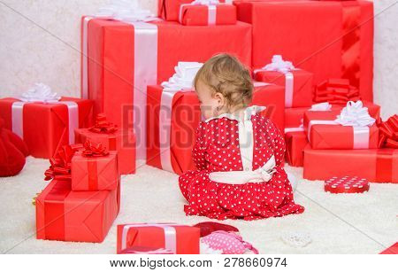 Little Baby Play Near Pile Of Wrapped Red Gift Boxes. My First Christmas. Sharing Joy Of Baby First