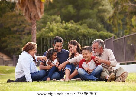Happy three generation Hispanic family sitting on the grass together in the park, selective focus