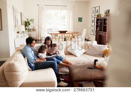 Young Hispanic family sitting on sofa reading a book together in the living room, seen from doorway