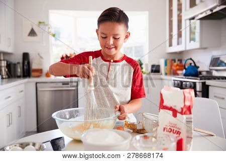 Pre-teen boy making a cake in the kitchen mixing cake mix, smiling, close up