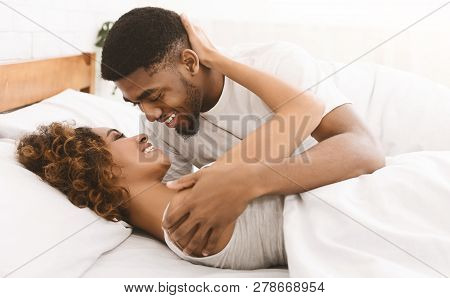 Happy Loving African-american Couple Relaxing On Bed At Home, Enjoying Togetherness And Tenderness I