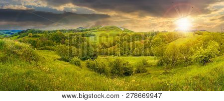 Beautiful Countryside Panorama In Springtime At Sunset. Grassy Hills And Meadows. Trees With Green F