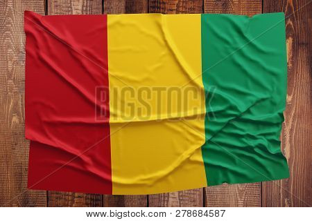 Flag Of Guinea On A Wooden Table Background. Wrinkled Guinean Flag Top View.
