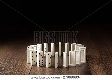Creative Background, White Domino, On Brown Wooden Background. Concept Of Domino Effect, Chain React