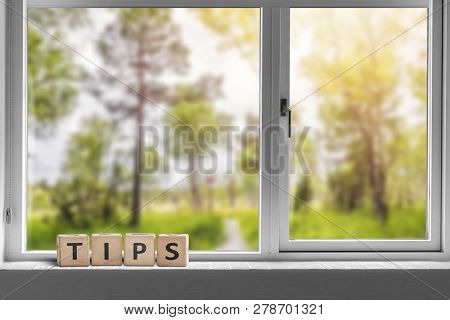 Tips Sign In A Window With A View To A Green Garden With Tall Trees In Sunlight