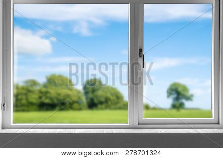 View From A Closed Window To A Green Meadow With Trees Under A Blue Sky