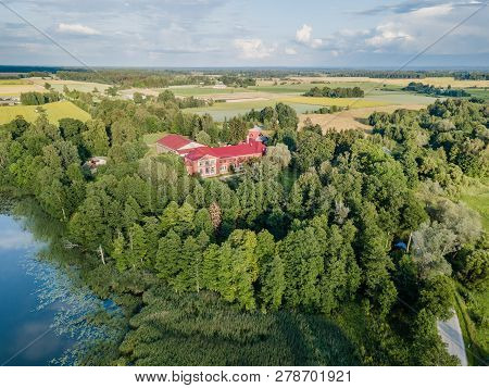 Aerial Photo Of Old Castle Turned Into School In Countryside Between Trees With Dramatic Clouds Over