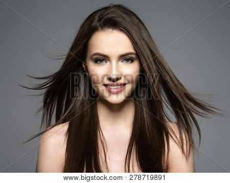 Brunette smiling woman with beauty long brown hair. Fashion model with long straight hair. Fashion model posing at studio. Pretty woman with long straight brown hair.