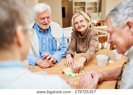 Senior couple and friends have fun playing board game in retirement home or at home