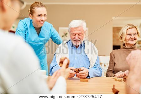 Nursing home care for seniors group with dementia in the puzzle game with wooden puzzle
