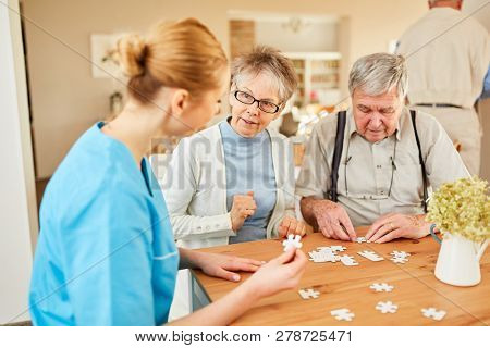 Nursing home helps a senior couple to play jigsaw puzzles at home or at home