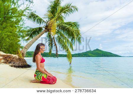 Tahiti Bora Bora French Polynesia Beach Vacation Travel Holidays. Woman relaxing sitting down on paradise beach on Matira Beach, Bora Bora. Happy girl wearing traditional pareo and Bikini in Tahiti