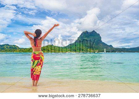 Vacation Travel woman walking on Tahiti paradise motu beach Bora Bora on holidays on Bora Bora with Mount Otemanu. Happy girl wearing traditional pareo and Bikini in Tahiti, French Polynesia.