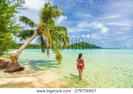 Vacation Luxury Travel woman walking on Tahiti paradise motu beach Bora Bora on holidays on Bora Bora with. Happy girl Bikini in Tahiti, French Polynesia.