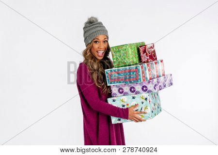 A gorgeous African American model posing with Christmas gifts against a white background in a studio environment