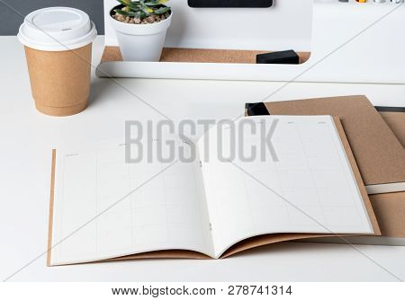 Top View Of Open Calendar Planner With Modern Office Stationery And Take Away Coffee Cup On White De