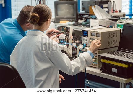 Team of electronic engineers testing a product prototype on test bench in the lab