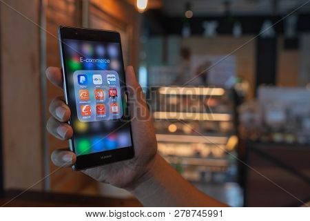 Chiang Mai, Thailand - June 09,2018: Man Holding Huawei With Icons Of E-commerce And Online Shopping