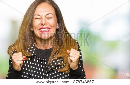 Beautiful middle age woman wearing fashion jacket excited for success with arms raised celebrating victory smiling. Winner concept.
