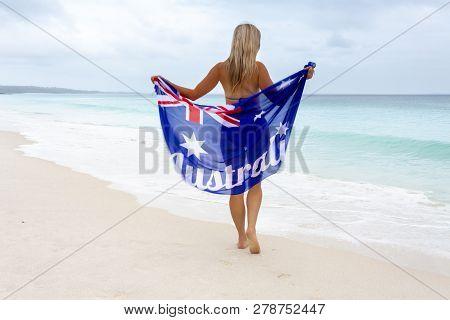 Australian Woman Walking Along A Beautiful Beach  Waves Washing Up To Her Feet, She Is Holding An Au
