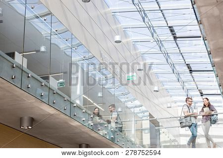 Low angle view of students talking while standing on glass floor at university campus