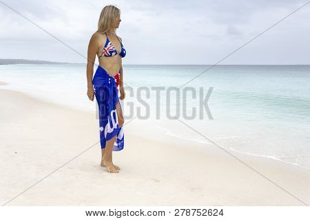 Woman With Australian Flag Draped Around Her On Beach