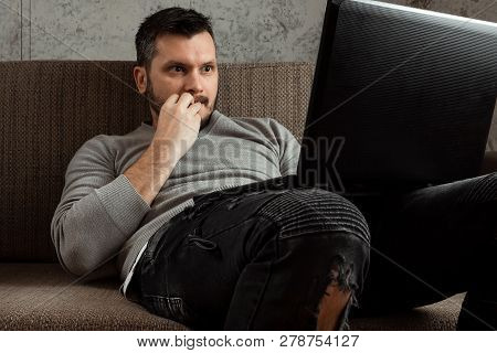 A Man Watches An Adult Video On A Laptop While Sitting On The Couch. The Concept Of Porn, Men's Need