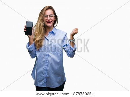 Young beautiful blonde business woman showing screen of smartphone over isolated background screaming proud and celebrating victory and success very excited, cheering emotion