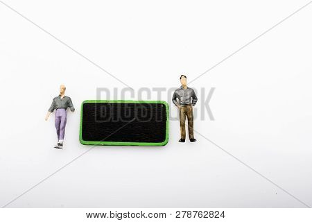 Two Figurine By A Black Noticeboard On A White Background