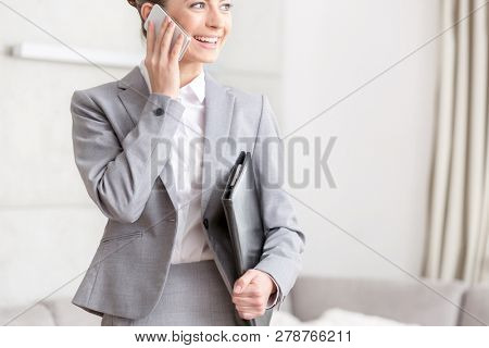 Midsection of smiling young saleswoman looking away while talking on smart phone in apartment