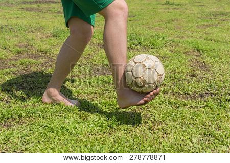 Barefoot Amateur Soccer Player On Old And Bad Field With Shabby Ball
