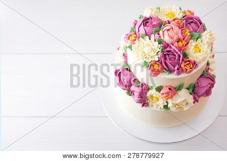 Two-tiered White Wedding Cake Decorated With Color Cream Flowers On A White Wooden Background. Top V