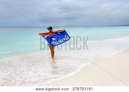 Aussie Culture.  A Woman Standis On A Stunning Beach Holding Proudly The Australian Flag.  Space For