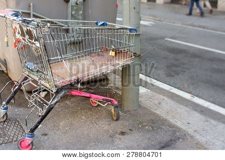 Homeless Shopping Cart Of A Beggar Chained To The Lamppost With A Padlock