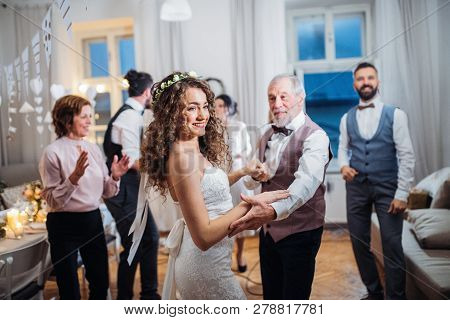 A Young Bride Dancing With Grandfather And Other Guests On A Wedding Reception.