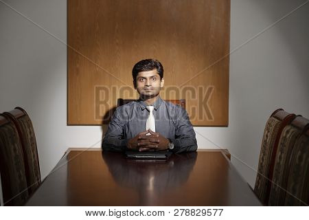 Confident Indina Company Ceo Sitting At The Head Of Table In Meeting Room