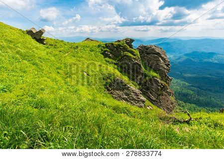 Rocky Formation On A Grassy Hillside. Path Among The Grass To The Boulders. Beautiful Mountain Ridge