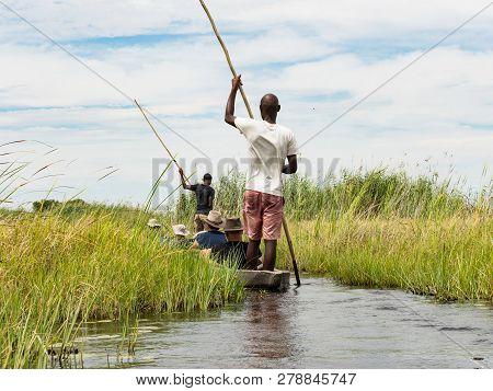 Mokoro Canoe Trip In The Okavango Delta Near Maun. Local Man Working On Mokoro To Deliver Tourists A