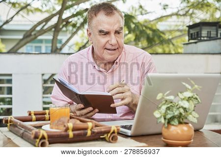 Senior Man Watching Lection On Laptop And Taking Notes In Textbook