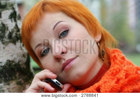 Young Red-Haired Woman In Red Scarf Is Talking In Mobile-Phone