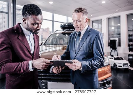 Businessman wearing business attire with tie signing documents poster