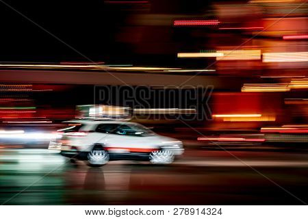 White Tax Cab Car In City With Motion Blur And Lights